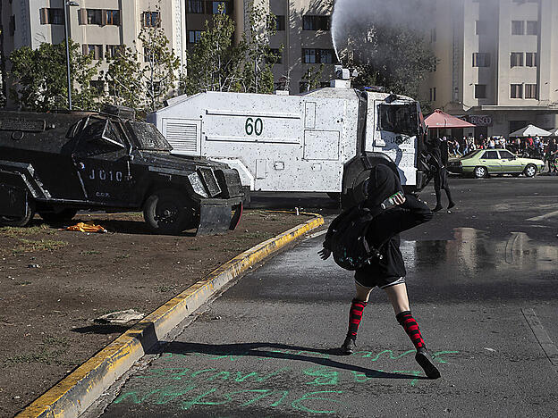 Eine Demonstrantin wirft eine Flasche auf einen Wasserwerfer der Polizei während einer Demonstration in Santiago de Chile am Internationalen Frauentag. Foto: Esteban Felix/AP/dpa